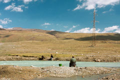 Blauwe kleurenrivier met sommige vissers in een bergvallei onder de bewolkte hemel Stock Foto