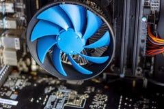 Blauwe koelere ventilator met motherboard binnen een computer stock fotografie