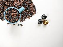 Blauwe koffiekop, met koffiebonen die, drie koffiecapsules, met witte achtergrond omringen Hoogste mening stock foto