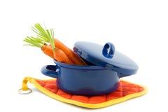 Blauwe kokende pan die met wortelen wordt gevuld Royalty-vrije Stock Afbeeldingen