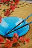 Blauwe kom met eetstokjes en takken Stock Afbeelding