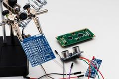 Blauwe kringsraad in het solderen van helpende handen stock foto