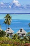 Blauwe lagune van het Eiland Bora Bora, Polynesia Een mening van hoogte op palmen, traditionele loges over water en het overzees Stock Afbeeldingen