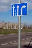 Blauwe lichte nadenkende verkeersteken met witte pijlen worden gevestigd Stock Afbeeldingen