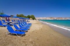 Blauwe ligstoelen op het openbare strand van Kreta Stock Foto's