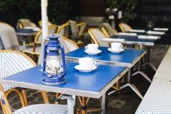 Blauwe lijst met kappen voor koffie op straat stock foto's