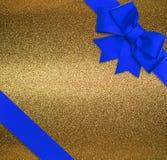 Blauwe lint en boog over glanzende gouden achtergrond Royalty-vrije Stock Afbeeldingen