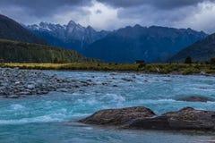 Blauwe meeslepende golven van verre rivier onder bergen stock foto's