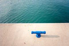Blauwe metaalmeerpaal door de haven stock fotografie