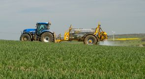 Blauwe moderne tractor die een gewassenspuitbus trekken Royalty-vrije Stock Foto's