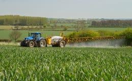 Blauwe moderne tractor die een gewassenspuitbus trekken Stock Afbeeldingen