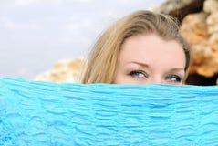Blauwe mooie ogen van het meisje achter blauwe sjaal Royalty-vrije Stock Afbeeldingen