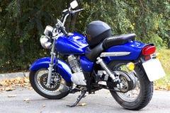 Blauwe motorfiets en zwarte helm Stock Afbeeldingen