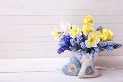 Blauwe muscaries en gele narcissenbloemen in vaas en twee DE Stock Foto's