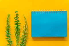 Blauwe notitieboekje Groene bladeren minimaal op Gele achtergrond royalty-vrije stock fotografie