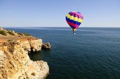 Blauwe Oceaan en Gele Klippen - Kleurrijke Hete Luchtballon Stock Foto's