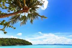 Blauwe oceaan en heldere blauwe hemel met kokospalm Royalty-vrije Stock Afbeeldingen