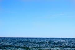 Blauwe Oceaan met Vlakke Horizon en Blauwe Hemel Stock Afbeeldingen