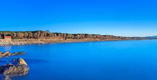 Blauwe oceaan, rotsen, pijnboom bos, duidelijke hemel, strand op zonsondergang Royalty-vrije Stock Fotografie