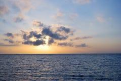 Blauwe oceaanzonsopgang bij bewolkt weer Stock Foto's