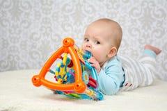 Blauwe ogenbaby die een stuk speelgoed bijten Royalty-vrije Stock Fotografie