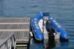 Blauwe opblaasbare die boot dichtbij de pijler wordt vastgelegd royalty-vrije stock fotografie