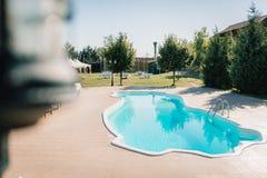 Blauwe openluchtpool in de tuin die door bomen wordt omringd stock fotografie