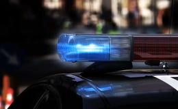 Blauwe opvlammende sirenes van politiewagen tijdens de wegversperring in c Stock Foto's