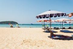 Blauwe overzees en parasol met sommige mensen Stock Foto's