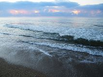 Blauwe overzees, golven met lammeren en strand met zeeschelpen stock foto
