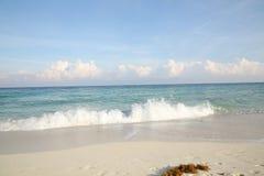 Blauwe overzees met schuimgolf, wit zand met voetafdrukken op het strand en blauwe hemel met wolken op de horizon royalty-vrije stock foto