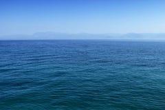 Blauwe overzees of oceaanwaterspiegel met horizon en hemel stock afbeeldingen