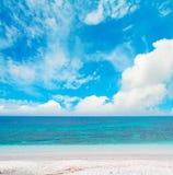 Blauwe overzees onder wolken stock afbeelding
