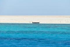 Blauwe overzees, wit strand en een zwart wrak 01 stock afbeeldingen