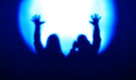 Blauwe paarsilhouetten met handen omhoog gezien schijnwerperbac Stock Fotografie