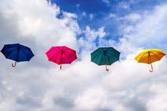 Blauwe Paraplu, Rode Paraplu, Groene Paraplu en Gele Paraplu die in de Lucht onder Blauwe Hemel en Wolken drijven Royalty-vrije Stock Foto's