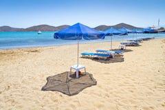 Blauwe parasols bij Egeïsche Overzees Stock Foto