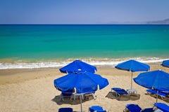 Blauwe parasols bij Egeïsche Overzees Stock Fotografie