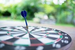 Blauwe pijltjepijl die in het doelcentrum raken van dartboard met g Stock Foto's