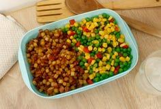 Blauwe plastic die voedselcontainer met voedsel wordt ingepakt stock foto's