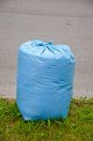 Blauwe plastic vuilniszak op straat Stock Afbeelding