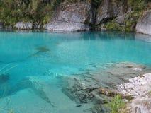 Blauwe pool die door rotsen wordt omringd stock foto's