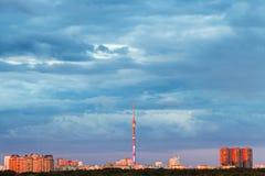 Blauwe regenachtige wolken over verlicht door zonsondergangstad Royalty-vrije Stock Foto