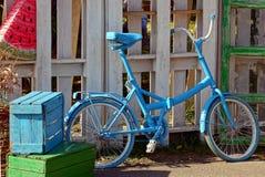 Blauwe retro fiets dichtbij een houten muur en verfdozen Royalty-vrije Stock Foto's