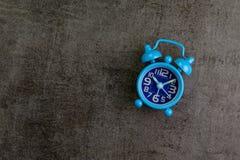 Blauwe retro wekker op de donkere zwarte muur die van de cementzolder als t gebruiken Stock Afbeeldingen