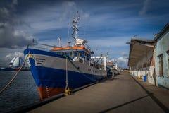 Blauwe, rode en witte geschilderde die vissersboot door de pijler op Hel-schiereiland, Polen wordt verankerd royalty-vrije stock fotografie