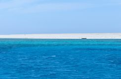 Blauwe Rode Overzees, bleek strand en een zwart wrak stock afbeeldingen