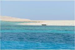 Blauwe Rode Overzees, bleek strand en een zwart wrak stock foto's