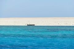 Blauwe Rode Overzees, bleek strand en een zwart wrak royalty-vrije stock foto's