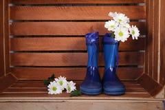 Blauwe rubberlaarzen met de lentebloemen stock foto